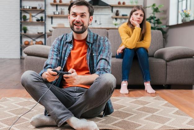 Mulher jovem triste olhando homem jogando videogame com joystick Foto gratuita