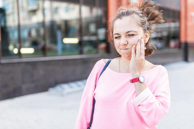 Mulher jovem triste, sofrendo de dor de dente grave enquanto caminhava na rua de verão. Foto Premium