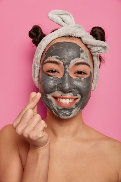 Mulher jovem usa máscara facial natural de argila para tratamentos de pele após o banho Foto gratuita