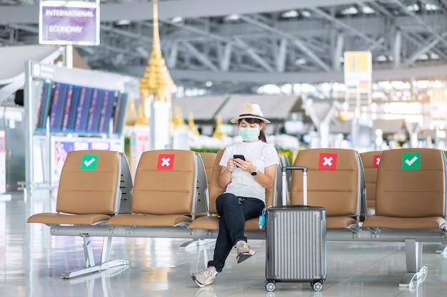 Mulher jovem usando máscara facial e usando smartphone móvel no aeroporto, infecção de doença de coronavirus (covid-19) de proteção, viajante asiático sentado na cadeira. novo normal e distanciamento social Foto Premium