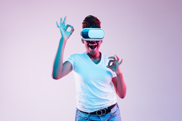Mulher jovem usando óculos vr com luzes de néon Foto gratuita