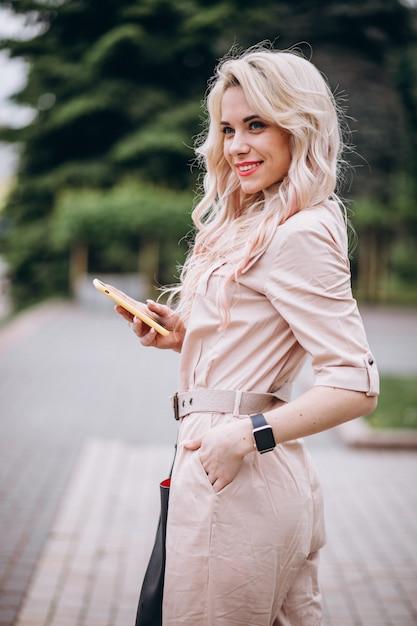 Mulher jovem, usando, telefone, exterior, parque Foto gratuita