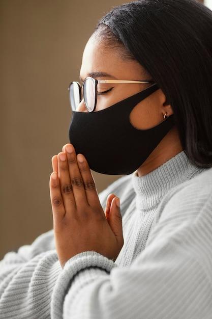 Mulher jovem usando uma máscara facial enquanto orava Foto gratuita