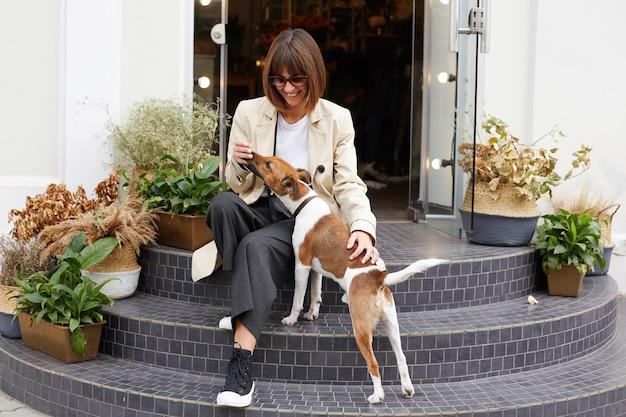 Mulher jovem vestida de maneira casual, sentada na escada do café, sorrindo, brincando com seu adorável cão de estimação jack russell terrier Foto gratuita