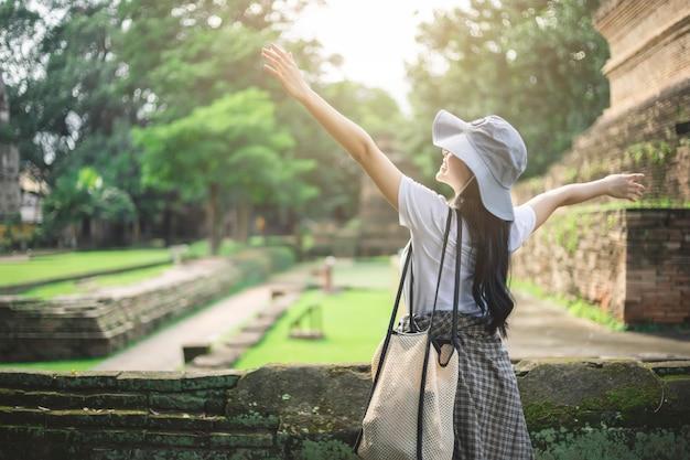 Mulher jovem viajante asiático sorrindo enquanto viaja ao redor do templo antigo tailandês Foto Premium