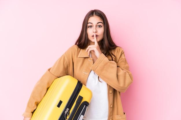 Mulher jovem viajante caucasiano segurando uma mala isolada, mantendo um segredo ou pedindo silêncio. Foto Premium