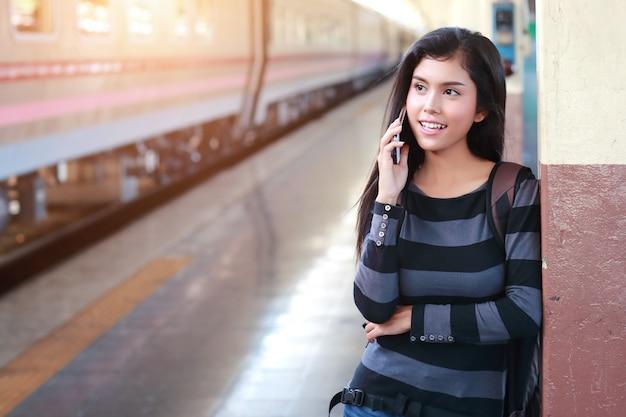 Mulher jovem viajante com mochila usando telefone inteligente durante a viagem de férias Foto Premium