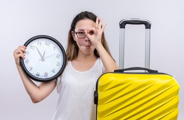 Mulher jovem viajante com uma camiseta branca em pé com uma mala segurando um relógio de parede fazendo uma placa de ok olhando através desta placa sobre a parede branca Foto gratuita