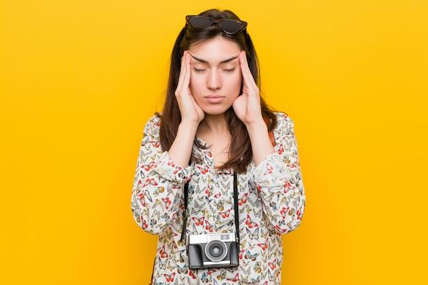Mulher jovem viajante morena tocando os templos e tendo dor de cabeça. Foto Premium