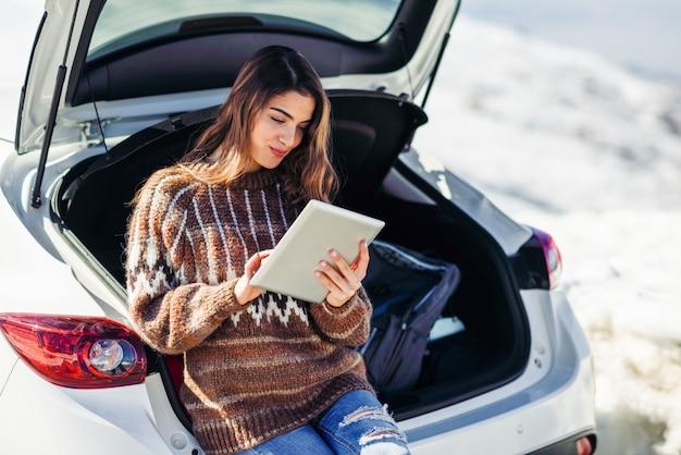 Mulher jovem viajante usando computador digital nas montanhas nevadas no inverno. Foto Premium