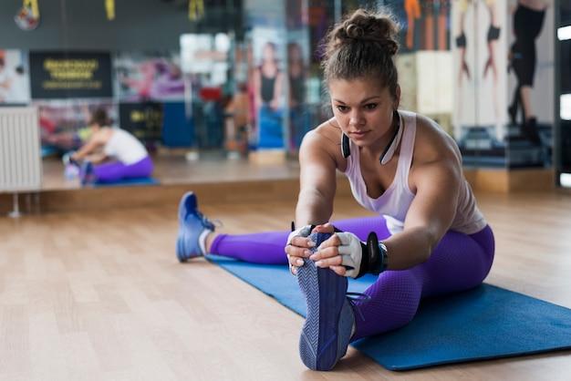 Mulher jovem, warming-up, em, ginásio Foto gratuita