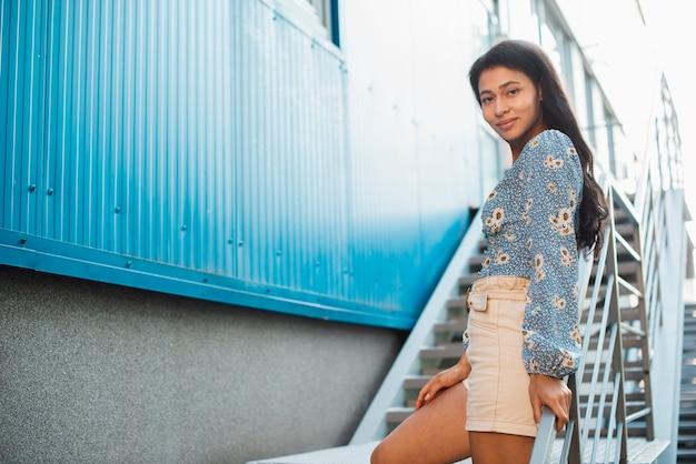 Mulher lateral de vista baixa em calças brancas e camisa floral Foto gratuita