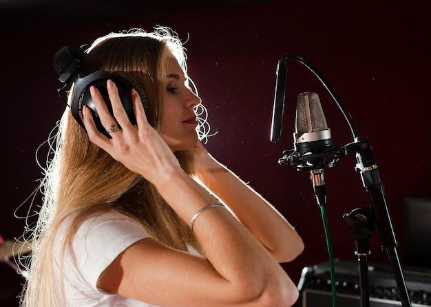Mulher lateral se preparando para cantar sua parte Foto gratuita