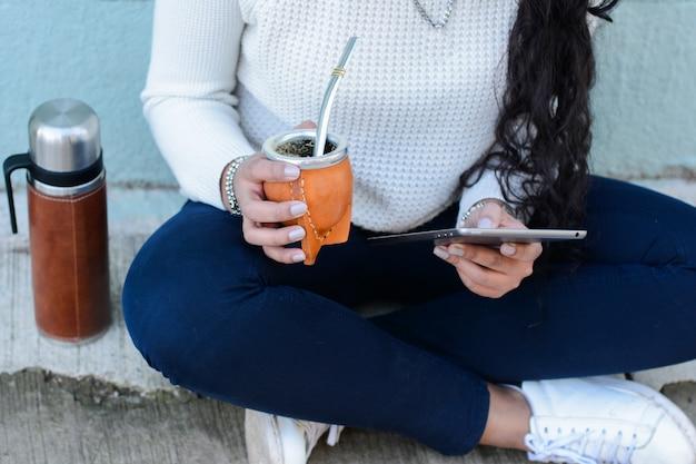 Mulher latin nova que bebe o chá tradicional do companheiro do yerba com tabuleta Foto Premium