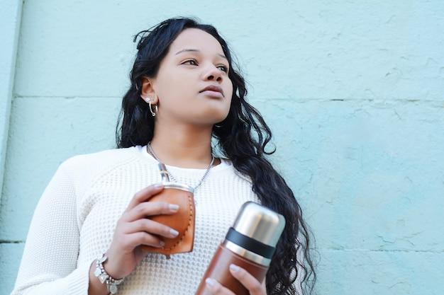Mulher latin nova que bebe o chá tradicional do companheiro do yerba. Foto Premium