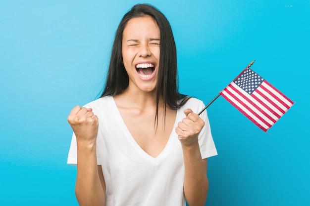 Mulher latino-americano nova que guarda um estados unidos embandeira torcendo despreocupado e entusiasmado. vitória. Foto Premium
