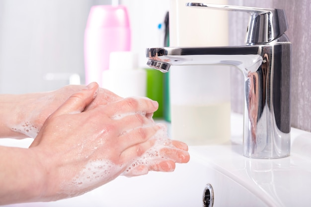 Mulher lava as mãos com sabão debaixo da torneira em uma moderna casa de banho Foto Premium