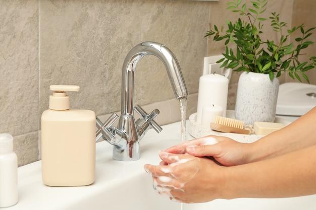 Mulher lavando as mãos embaixo da torneira da pia Foto Premium