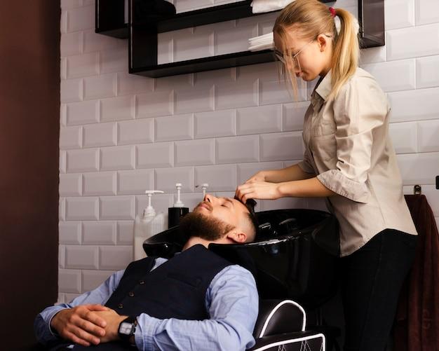 Mulher lavando o cabelo de um homem na barbearia Foto gratuita