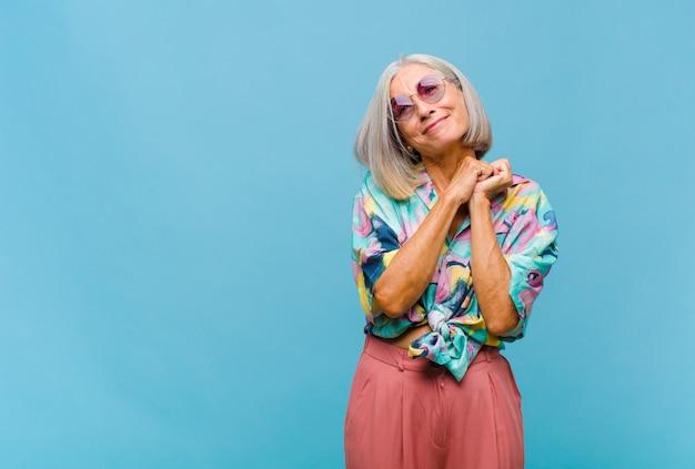 Mulher legal de meia-idade se sentindo apaixonada e bonita, adorável e feliz, sorrindo romanticamente com as mãos ao lado do rosto Foto Premium