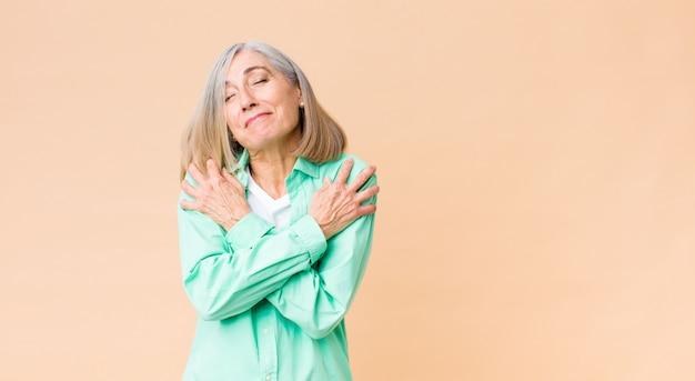 Mulher legal de meia-idade se sentindo apaixonada, sorrindo, acariciando e abraçando a si mesma, permanecendo solteira, sendo egoísta e egocêntrica Foto Premium