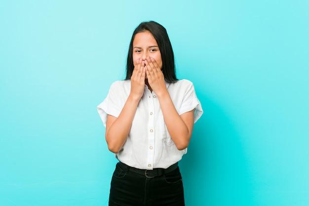 Mulher legal latino-americano nova contra uma parede azul que ri sobre algo, cobrindo a boca com as mãos. Foto Premium