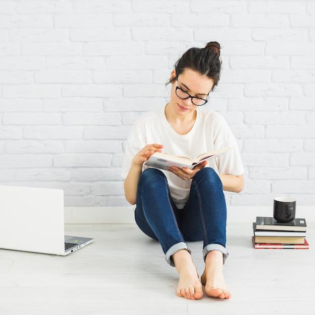 Mulher, leitura, perto, laptop, e, copo Foto gratuita