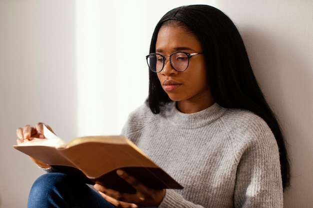 Mulher lendo a bíblia dentro de casa Foto gratuita