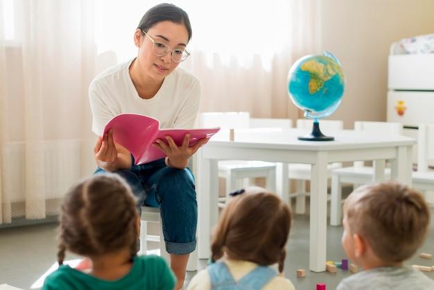 Mulher lendo algo para seus alunos Foto gratuita