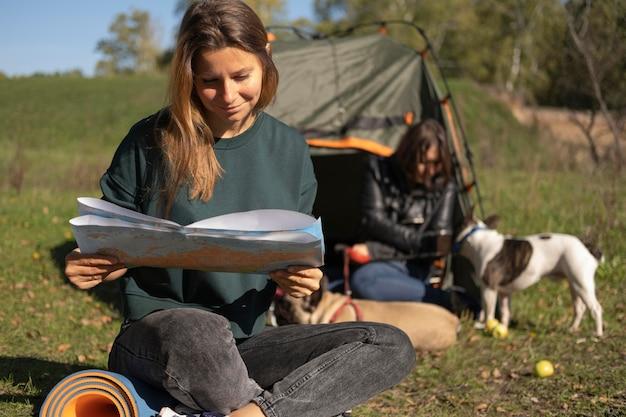 Mulher lendo e cachorrinho brincando com a amiga Foto gratuita