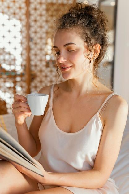 Mulher lendo e tomando café Foto gratuita