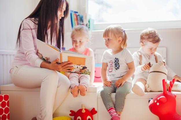 Mulher lendo para crianças na escola Foto gratuita