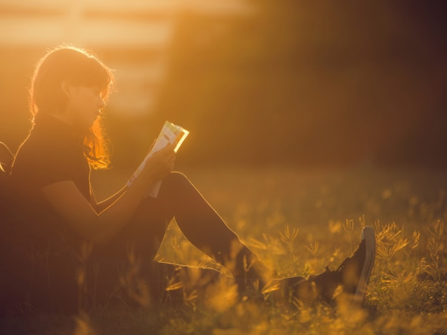 Mulher lendo um livro ao ar livre. ela está na universidade Foto Premium