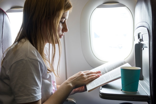 Mulher, lendo um livro, em, um, avião Foto gratuita