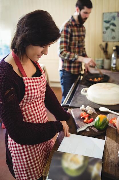 Mulher, lendo um livro receita, em, cozinha Foto gratuita