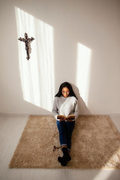 Mulher lendo um livro sagrado dentro de casa Foto gratuita