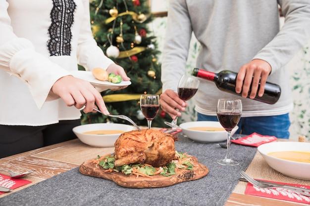 Mulher, levando, galinha assada, de, tabela natal Foto gratuita