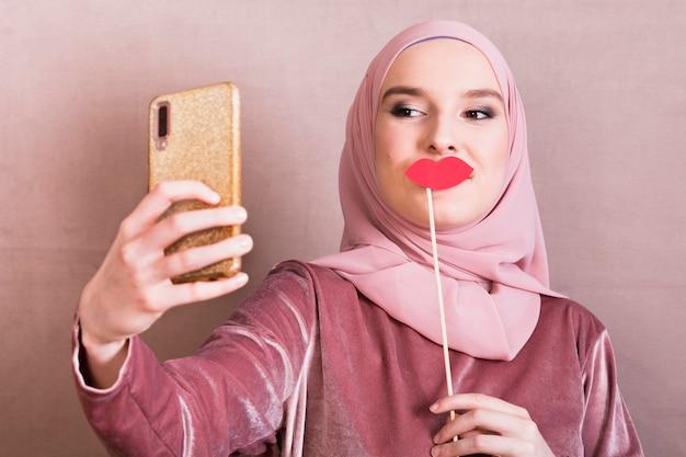 Mulher, levando, selfie, ligado, smartphone, com, amuo, lábios, prop Foto gratuita