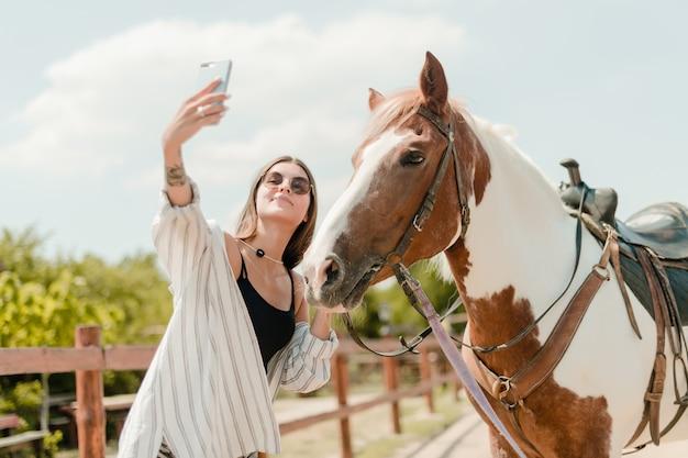 Mulher, levando, selfie, ligado, um, telefone, com, um, cavalo, ligado, um, fazenda Foto Premium