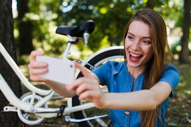 Mulher, levando, selfie, perto, bicicleta Foto gratuita