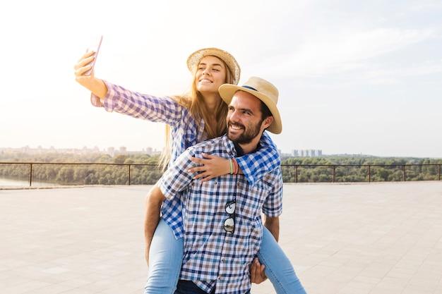 Mulher, levando, selfie, tendo, piggyback, ligado, dela, boyfriend's, costas Foto gratuita