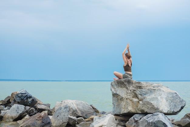 Mulher levanta os braços para o céu na postura namastê e senta-se na posição de lótus. Foto Premium