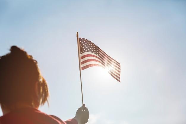 Mulher, levantando bandeira americana, para, sol brilhante Foto gratuita