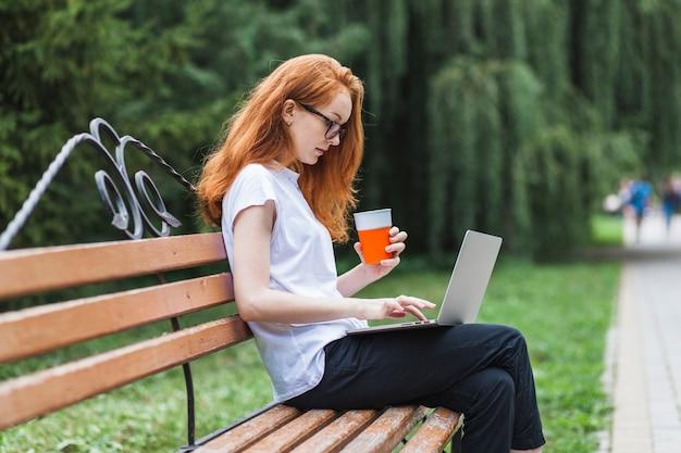 Mulher, ligado, banco, com, laptop, e, suco Foto gratuita