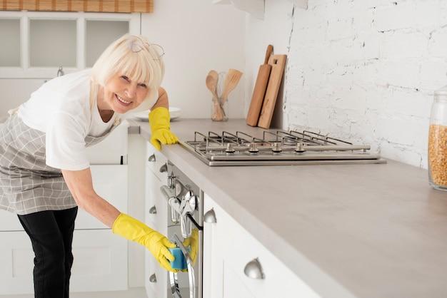 Mulher limpando a cozinha com luvas Foto gratuita