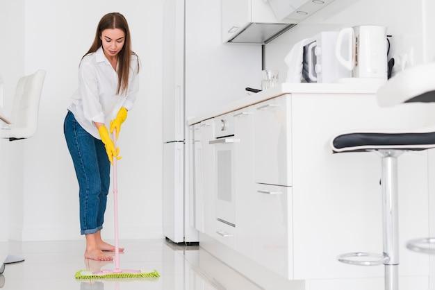 Mulher limpando a cozinha com uma esfregona visão de longo prazo Foto Premium