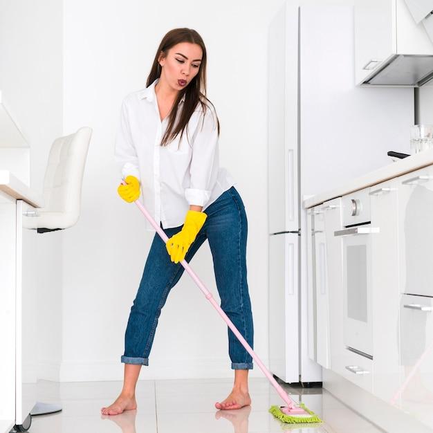 Mulher limpando a cozinha com uma esfregona Foto Premium