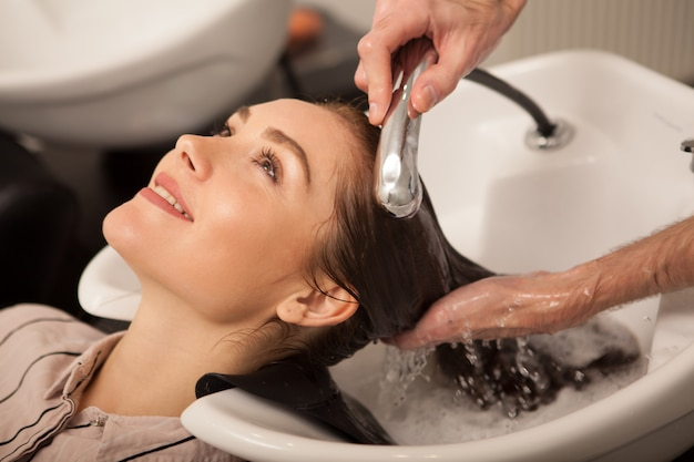 Mulher linda com o cabelo lavado pelo cabeleireiro Foto Premium