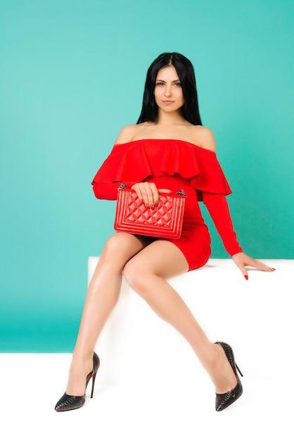 Mulher linda com vestido vermelho e bolsa bolsa com sapatos de salto alto sentada no banco branco - imagem Foto Premium