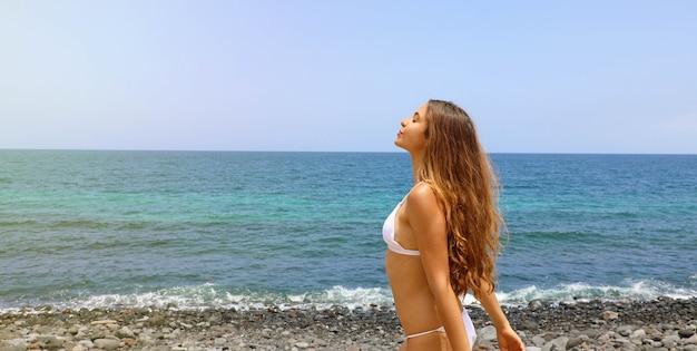 Mulher linda e despreocupada respirando fundo na praia Foto Premium